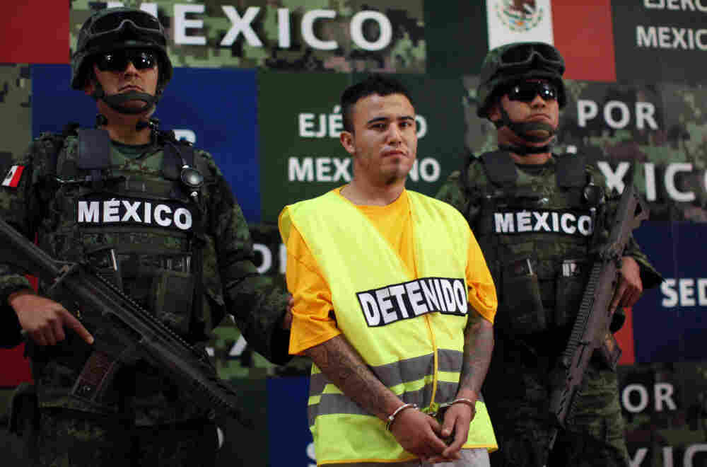"Army soldiers flank Daniel Ramírez, alias ""El Loco,"" during his presentation to the media in Mexico City on Monday."