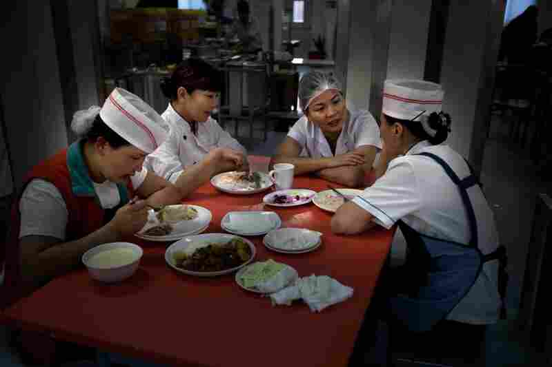 Kitchen workers take a break after the morning rush at the cafeteria, which feeds thousands of workers every day.