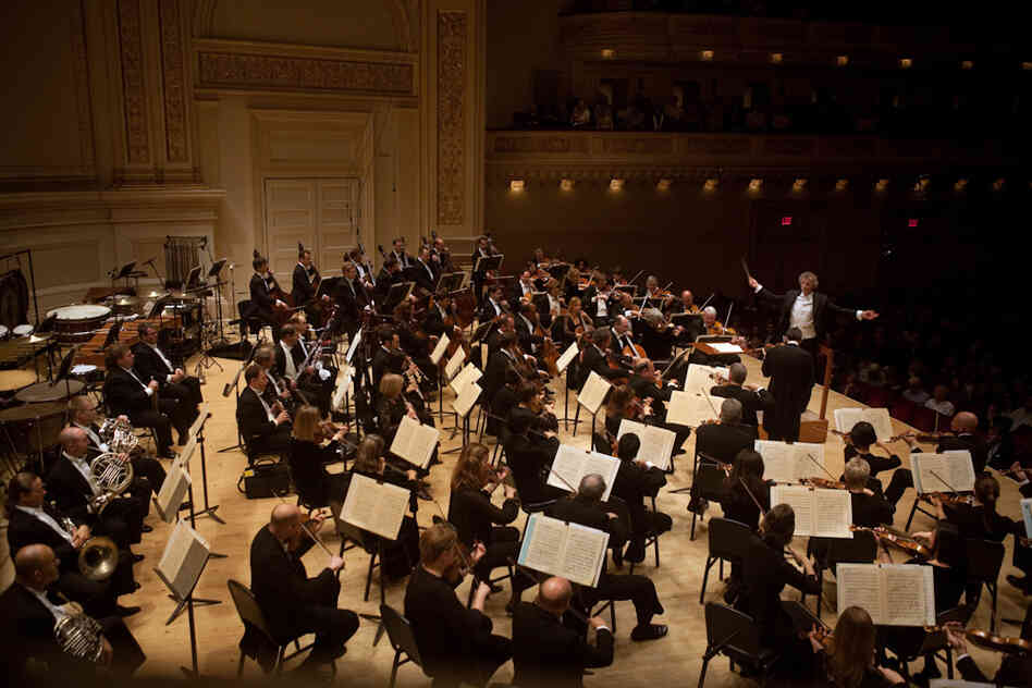 The Cleveland Orchestra's concert at Carnegie Hall on May 23, 2012 was originally scheduled to include Shostakovich's Symphony No. 6, Kaija Saariaho's 'Laterna Magica,' and Brahms' Piano Concerto No. 2 with Yefim Bronfman. However, after Bronfman cancelled due to illness about 24 hours before concert time, violinist Gil Shaham stepped in to play the Brahms Violin Concerto.
