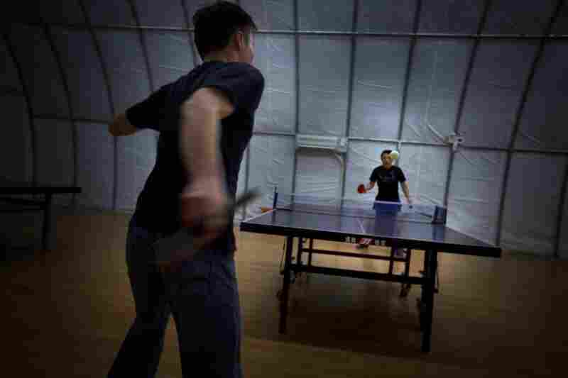 Mine workers play table tennis inside a Quonset hut.