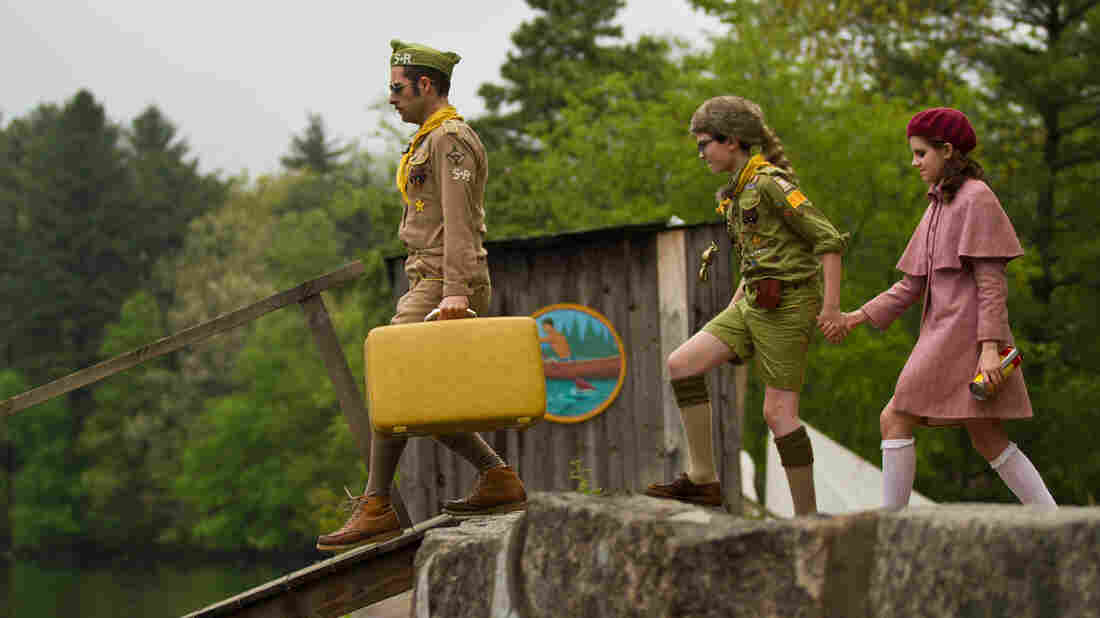 Cousin Ben (Jason Schwartzman) leads Sam (Jared Gilman) and Suzy (Kara Hayward) down a dock in Moonrise Kingdom. The film, set in 1965, follows Sam and Suzy when they elope together into the wilderness of the fictitious New Penzance island.