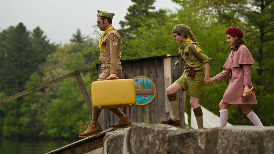 Cousin Ben (Jason Schwartzman) leads Sam (Jared Gilman) and Suzy (Kara Hayward) down a dock in <em>Moonrise Kingdom</em>. The film, set in 1965, follows Sam and Suzy when they elope together into the wilderness of the fictitious New Penzance island.