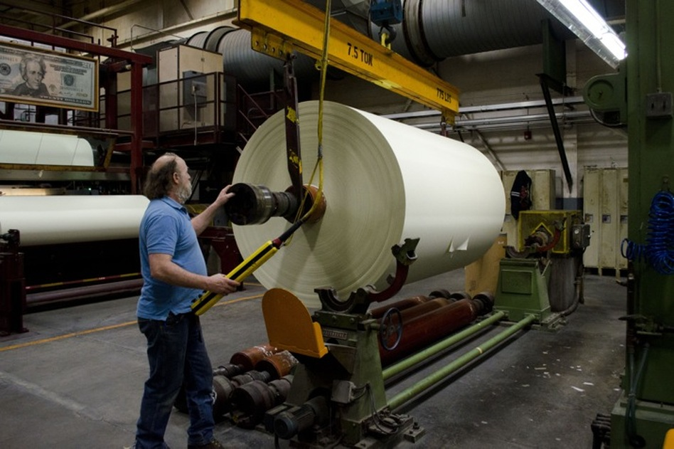 Rewinder operator John Danylieko moves a finished roll of currency paper from the paper machine. The roll will be cut into three narrower rolls before being cut into sheets. (NPR)
