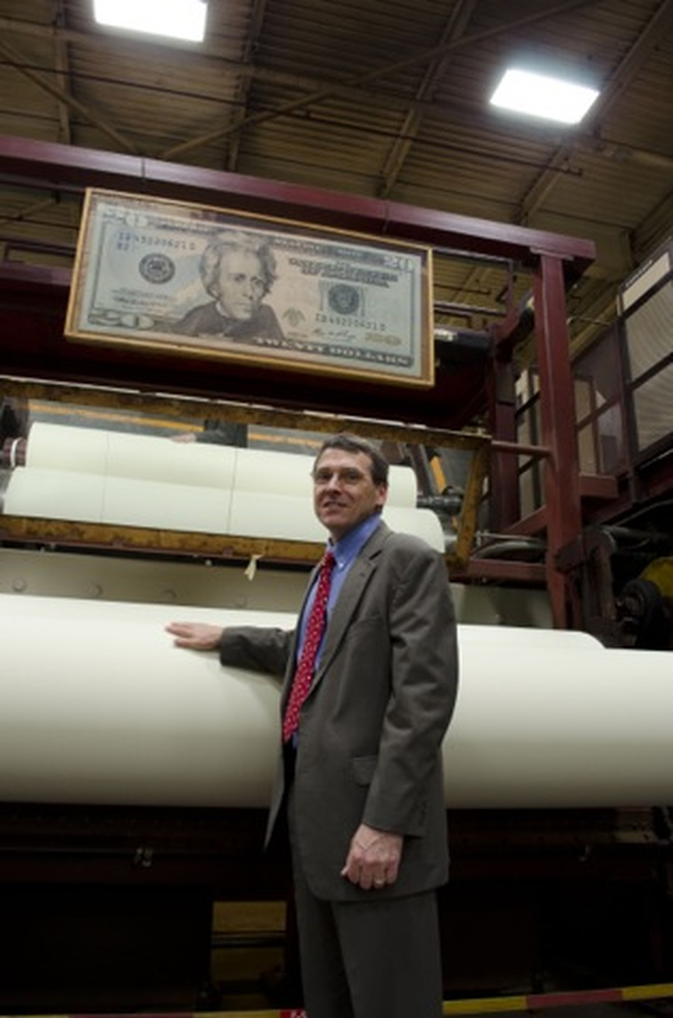 Crane & Co. Vice President Doug Crane stands near a spool of paper used for $20 bills, as it spins at the company's Wahconah Mill. (NPR)