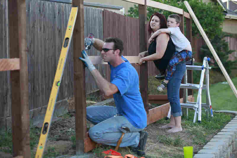 After coming home from his job, Kevin works on a fence he is building around their home. The Coopers have stopped taking trips, eating out and spending money on anything else they don't need.