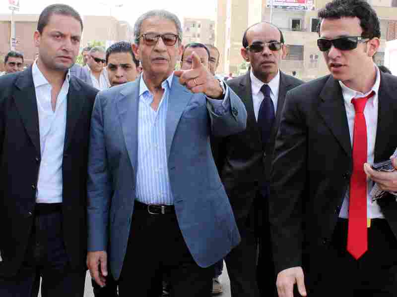 Former Egyptian Arab League chief and presidential candidate Amr Mussa (2nd L) arrives at a polling station to vote in Cairo on May 23, 2012, during the country's historic presidential election, the first since a popular uprising toppled Hosni Mubarak.