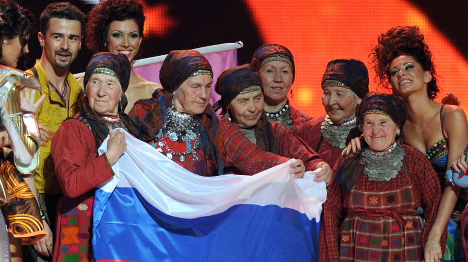 Russia's singing group Buranovskiye Babushki hold their national flag as they celebrate making it through to the Eurovision final on May 22 with Moldova's entrant, Pasha Parfeny (left), and his dancers.