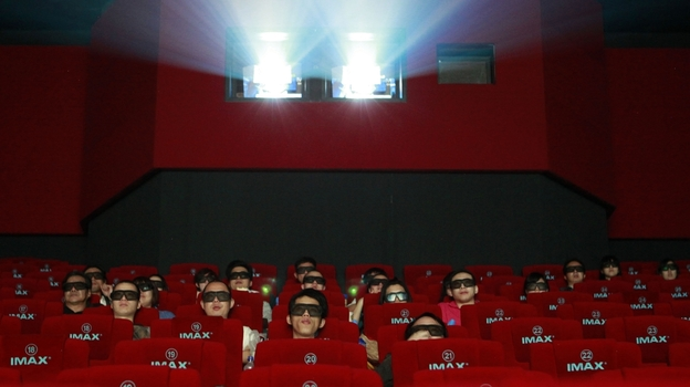 Moviegoers watch a 3-D IMAX movie at a Beijing theater run by the Chinese company Wanda, which recently announced it was buying AMC movie theaters for $2.6 billion. The move is seen as part of a larger effort by the Chinese conglomerate to move into the U.S. market. (AP)