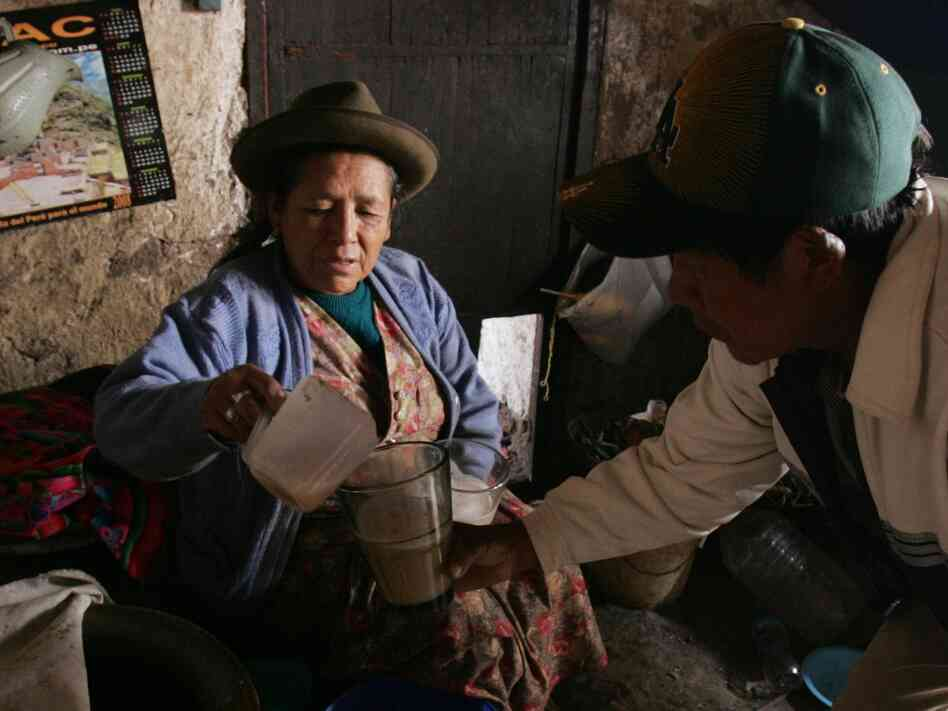A woman serves a glass of 'Chicha' to a client in the village of Pisaq near Cuzco, Peru. Chicha is a local alcoholic beverage made from sprouted or germinated corn.