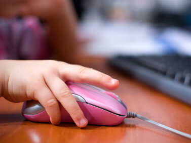 Child's hand on a pink computer mouse.