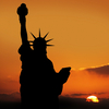 The Statue of Liberty silhouetted by sunset in New York City.