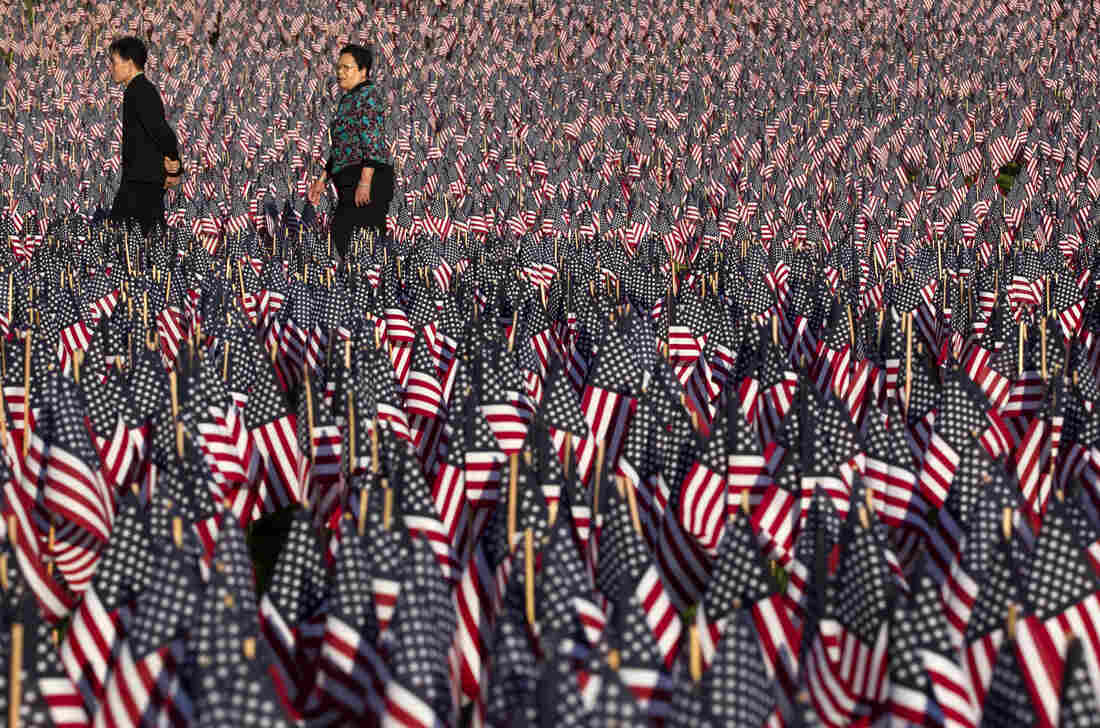 People walk through a portion of the Boston Common covered with American flags on Wednesday.