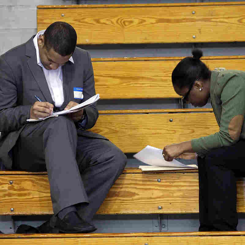 Job seekers fill out applications at a job fair in the Queens borough of New York City earlier this month. Economists say jobs in the middle — in sales, administration and assembly, for example — are being squeezed.
