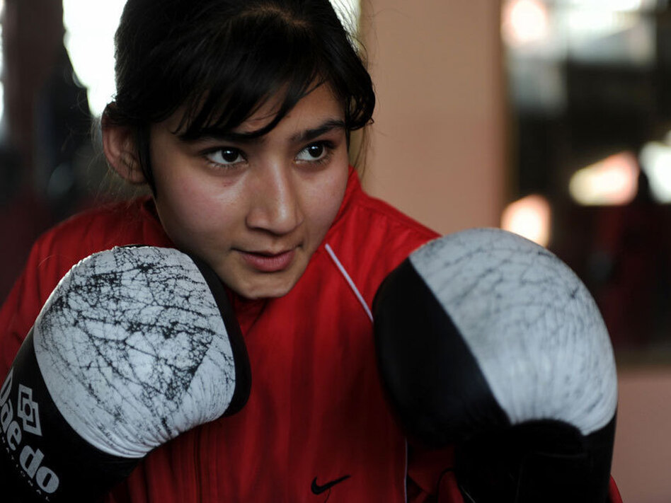 An Afghan girl takes part in a boxing training session around in a training room at the Kabul stadium, in Kabul in January 2011.