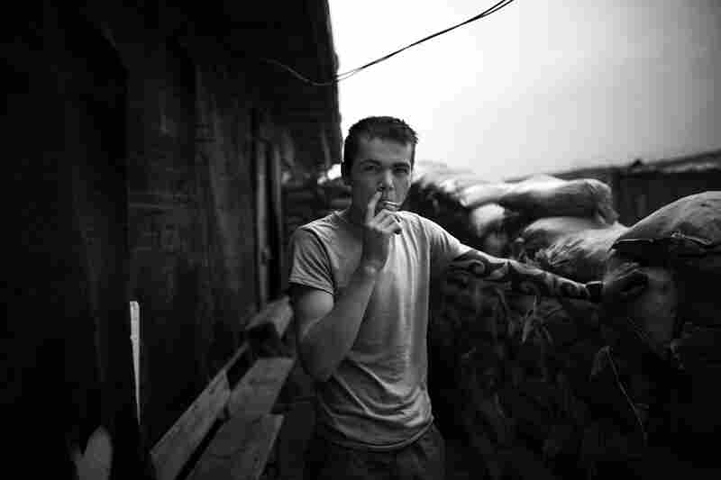 Derik Moe, of Pasco, Wash., smokes a cigarette behind the sandbag walls of makeshift sleeping quarters, located in an old office building.