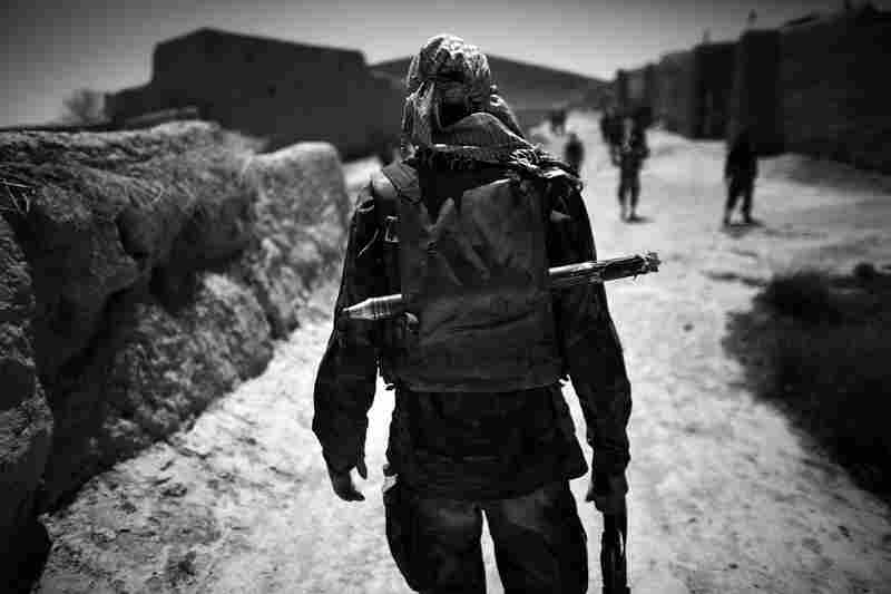 An Afghan soldier carries a backpack filled with extra ammunition and a spare rocket-propelled grenade while on a joint operation foot patrol with soldiers from the 82nd Airborne.