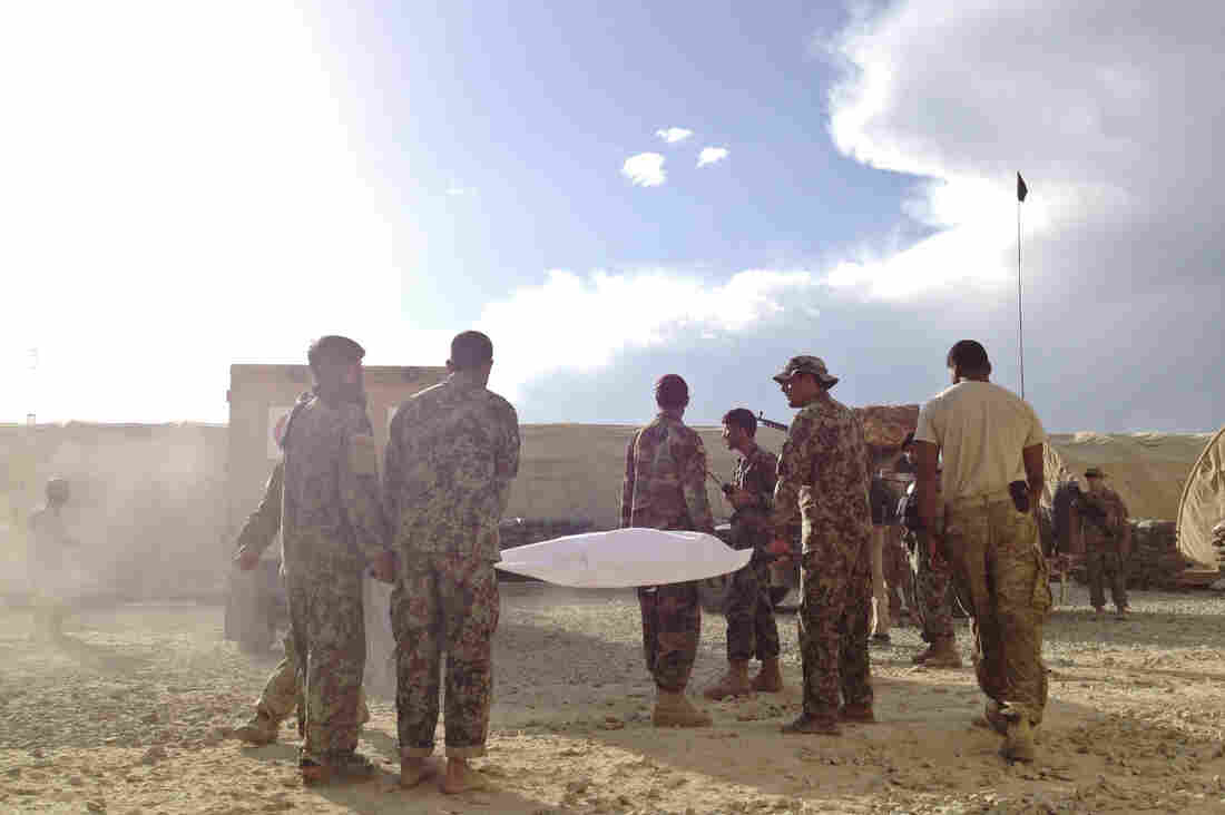 The body of Afghan soldier Burhan Muddin is carried to an ambulance in eastern Afghanistan's Ghazni province. He was shot while on guard duty at an Afghan army outpost near the U.S. base. He was brought to the Americans for medical treatment, but U.S. forces were unable to save him.