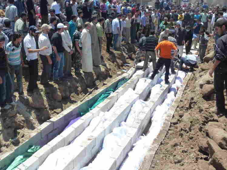 Saturday: In this picture provided by the Syrian opposition's Shaam News Network, people watch the mass burial of vic