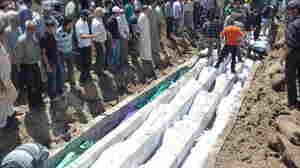 Saturday: In this picture provided by the Syrian opposition's Shaam News Network, people watch the mass burial o