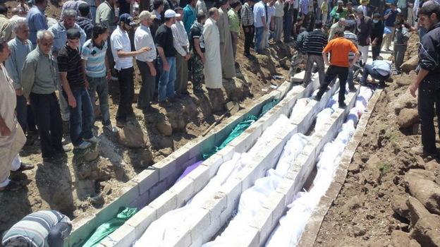 Saturday: In this picture provided by the Syrian opposition's Shaam News Network, people watch the mass burial of victims from Friday's violence in Houla. (AFP/Getty Images)