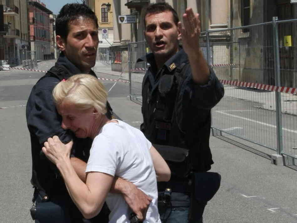 Two police officers in Mirandola try to comfort a woman after today's eart