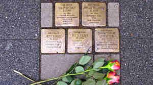 """Brass bricks known as Stolperstein, or """"stumbling stones,"""" in front of a home in Raesfeld, Germany, where five members of a single family were forcibly removed by the Nazis. Across Germany, the stones commemorate the millions of victims of the Nazi regime."""