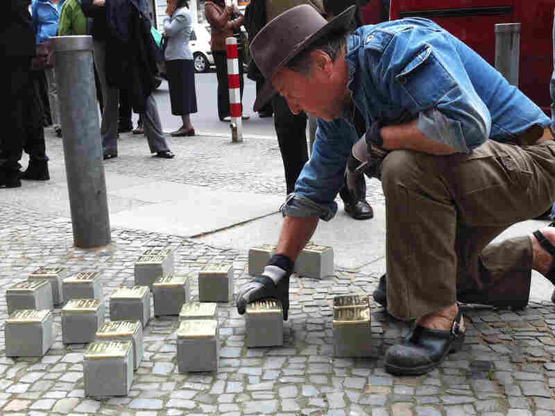 "Guenther Demnig is the artist and sculptor behind the stumbling stones. Here, he installs new bricks in Berlin. He says formal memorials are too abstract. Not so with the stumbling stones. ""Suddenly they are there, right outside your front door, at your feet, in front of you,"" he says."