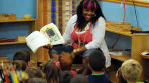 Kimberly Payton, a teacher at the Small Savers Child Development Center, reads to a group of preschoolers in Washington, D.C., in 2010. Researchers say that teachers who make small changes in how they read to 4-year-olds can improve kids' reading skills later on.