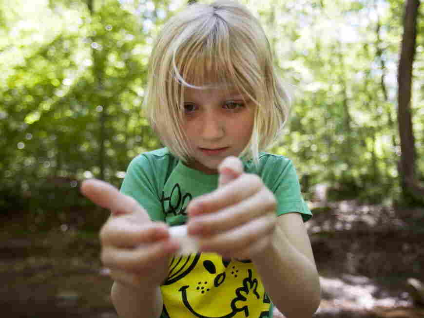 Lori Anne Madison, 6, studies a snail while also giving an interview to The Associated Press about being the youngest-ever competitor in the National Spelling Bee.