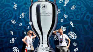 Larger Than Life: Tourists pose in front of a UEFA Euro 2012 Cup placard on Kiev's Independence Square in Ukraine. Europe is entering a packed sports schedule — but soccer still reigns supreme, says Frank Deford.
