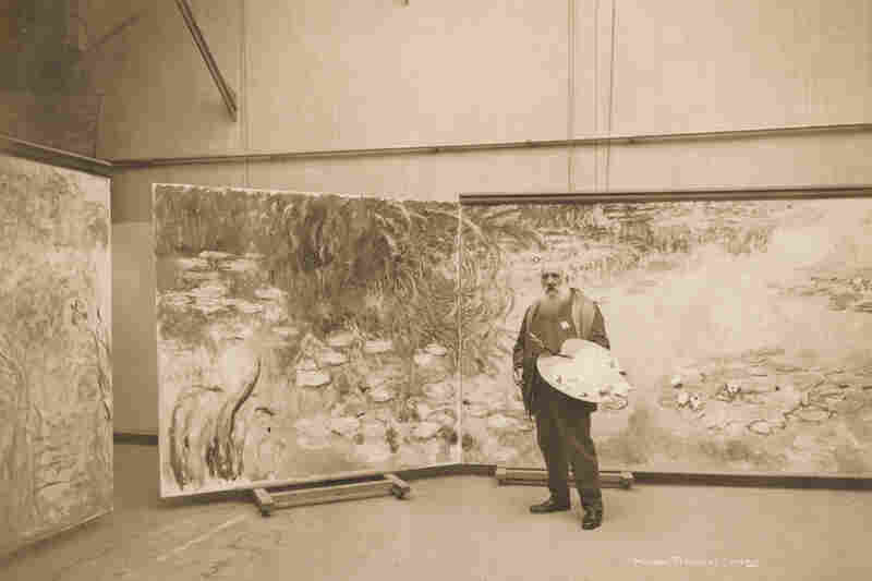 Monet works on one of his many water lily paintings in his studio at Giverny in 1920.