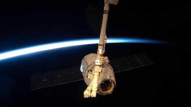 The SpaceX Dragon module, held by the International Space Station's robotic arm.