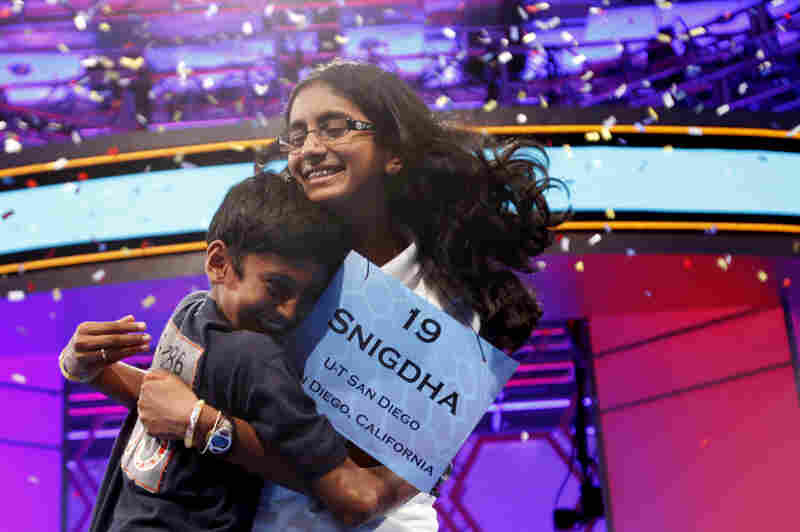 """With confetti falling, Snigdha Nandipati, 14, is embraced by her brother, Sujan Nandipati, after she won the National Spelling Bee with the word """"guetapens"""" Thursday."""