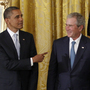 President Barack Obama gestures toward former President George W. Bush, former first lady Laura Bush and first lady Michelle Obama, at the White House in Washington, Thursday, during a ceremony where the Bushs' portraits were unveiled.