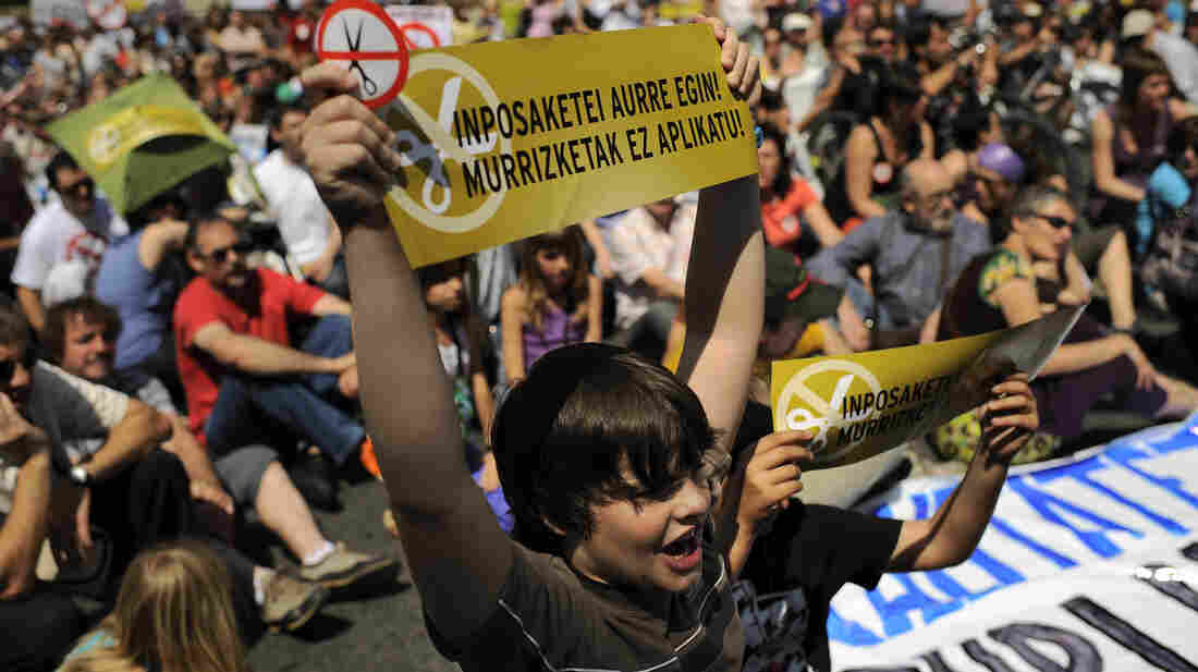 A student in Pamplona, holding a sign in the Basque language, protests cuts Thursday in education and other public services by the government. Spain's financial position is weakening and there are fears the country will need a bailout.