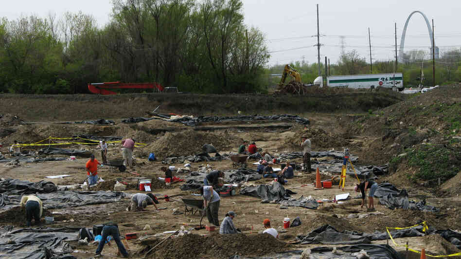 Archaeologists and crew members from the Illinois State Archaeological Survey work at an East St. Louis dig site, which is believed to be a suburb of the ancient city of Cahokia. Black plastic sheeting protects the excavations. In the distance, construction crews are building a stretch of inters
