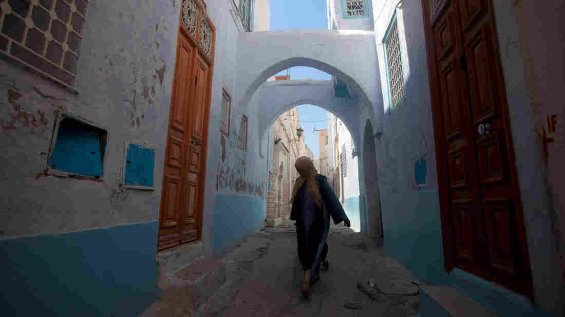 A woman walks the narrow streets of the old city in Kairouan.
