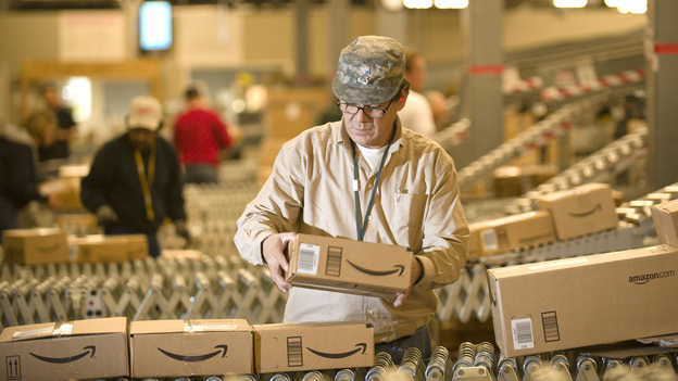 An Amazon worker grabs boxes off a conveyor belt in Nevada, one of a <a href=