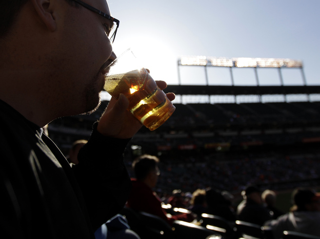 Sunlight shines through Brandon Butler's beer as he takes a sip during the first baseball game of a doubleheader between the Orioles and the Texas Rangers in Baltimore on May 10.