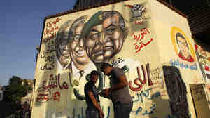 An Egyptian man paints the national flag on the arm of a friend as they stand in front of graffiti showing the morphed faces of ousted Egyptian President Hosni Mubarak (right) and military ruler Hussein Tantawi, defeated presidential candidate Amr Moussa (second from left), and current candidate Ahmed Shafiq (left) near Cairo's central Tahrir Square last month.