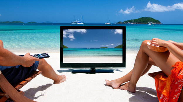 Two people watching TV at the beach.