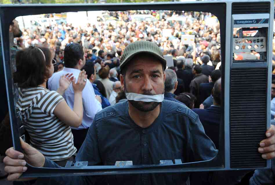 A Tunisian journalist holds a TV frame as part of a protest in Tunis against actions taken against the media. Since last