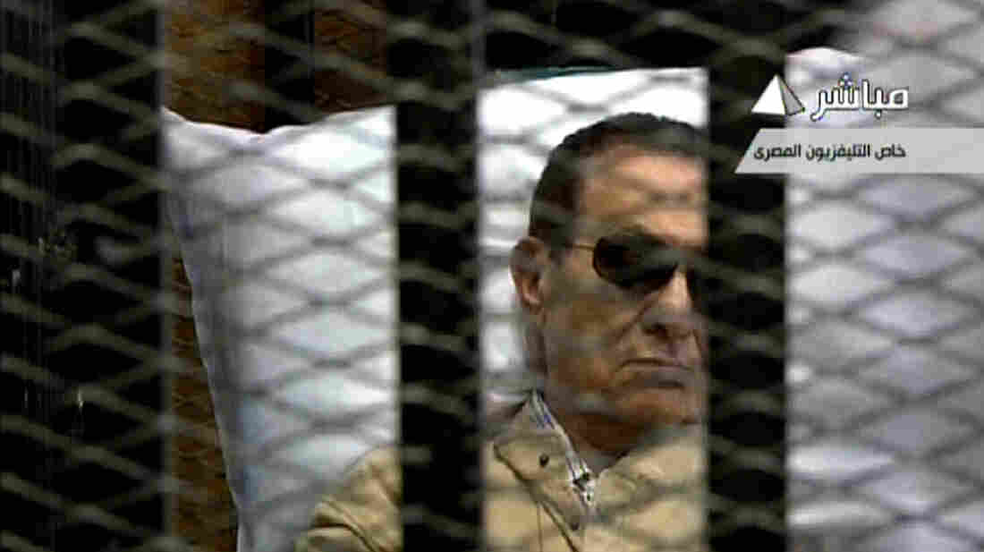 An image grab taken from Egyptian state TV shows ousted Egyptian president Hosni Mubarak sitting inside a cage in a courtroom during his ver