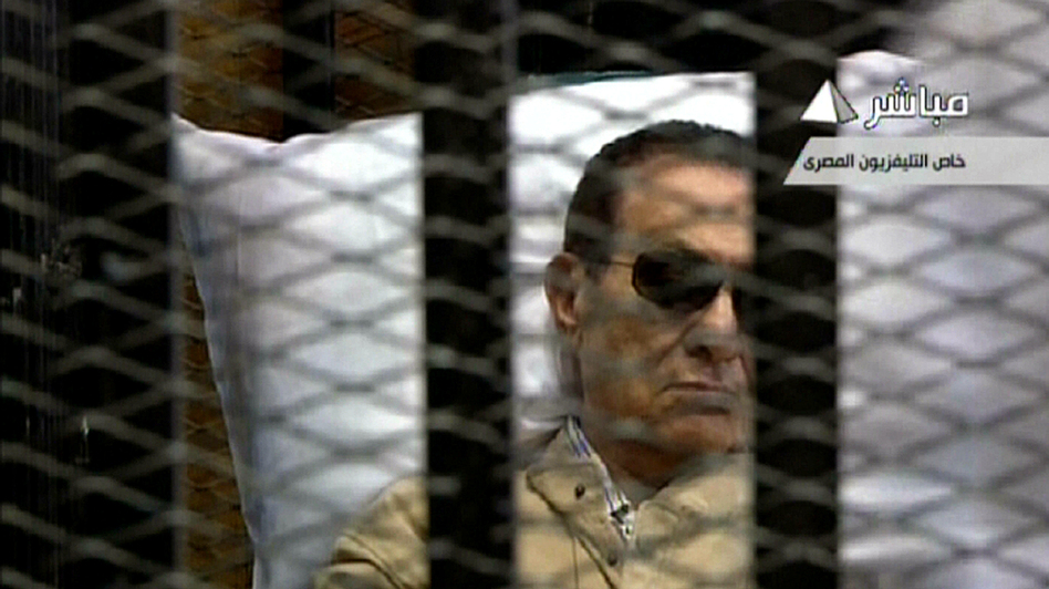 An image grab taken from Egyptian state TV shows ousted Egyptian president Hosni Mubarak sitting inside a cage in a courtroom during his verdict hearing in Cairo Saturday. (AFP/Getty Images)