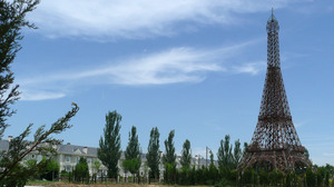 A rusting model of the Eiffel Tower stands at one end of the theme park, surrounded by construction debris and empty housing outside the park.