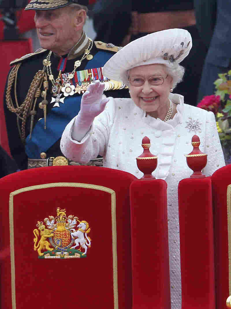 The queen wore a silver and white dress and matching coat — embroidered with gold, silver and ivory spots and embellished with Swarovski crystals to evoke the river — for her trip.
