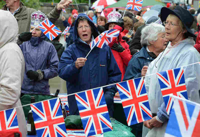 Crowds swelled into the thousands, with revelers in hats, flags, leggings and rain ponchos adorned with the Union flag mixing with burger and cotton-candy vendors along the 7-mile route along the Thames.