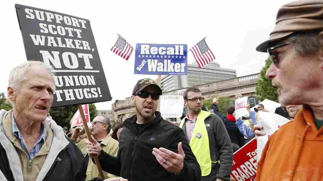 A supporter of Wisconsin Gov. Scott Walker (right) talks with a supporter of Walker's Democratic opponent, Tom Barrett, at a recall election rally Friday on Friday.