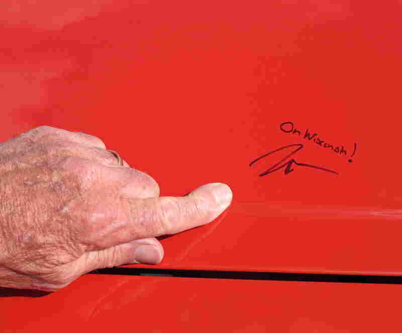 Stan Larson, 81, of Menomonee Falls, Wis., points to the hood of his 1965 Mustang, autographed by Wisconsin Gov. Scott Walker during a campaign stop Sunday in Germantown, Wis.