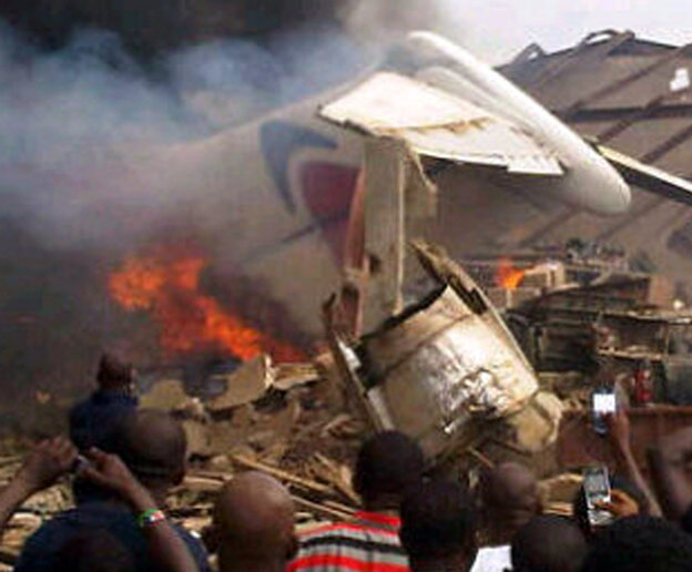 A picture taken with a photo camera shows residents of the Iju district of Lagos, Nigeria,  gathering at the site where a Dana Air jet crashed into a neig